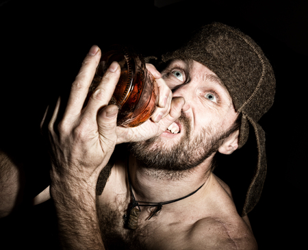 Dark portrait of scary evil sinister bearded man with smirk, holding a bottle of cognac. strange Russian man with a naked torso and a woolen hat.