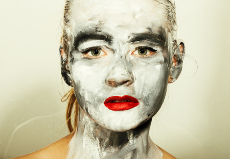 smeared: abstract art makeup. Face and neck girls smeared with gray colors and bright red lips. Holi Festival.