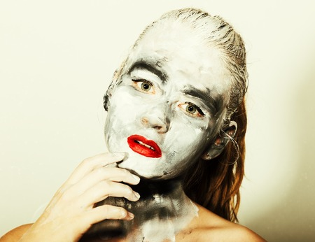 abstract art makeup. Face and neck girls smeared with gray colors and bright red lips. Holi Festival.