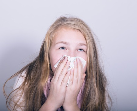 Sick young girl blowing her nose with paper tissue. Stock Photo