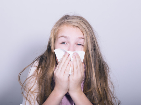 hanky: Sick young girl blowing her nose with paper tissue. Stock Photo