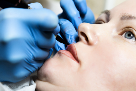 cosmetologist: Cosmetologist applying permanent make-up. Young beautiful woman having cosmetic tattoo on her lips. Healthy Spa.