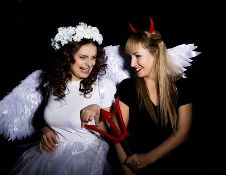 Portrait of angel and devil womans on a dark background. Stock Photo
