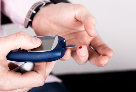 glycemic: Dependent first type diabetes patient. Measuring glucose level blood test using ultra mini glucometer and small drop of blood from finger and test strips.
