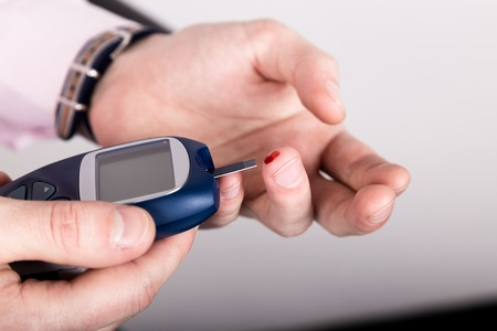 Dependent first type diabetes patient. Measuring glucose level blood test using ultra mini glucometer and small drop of blood from finger and test strips.