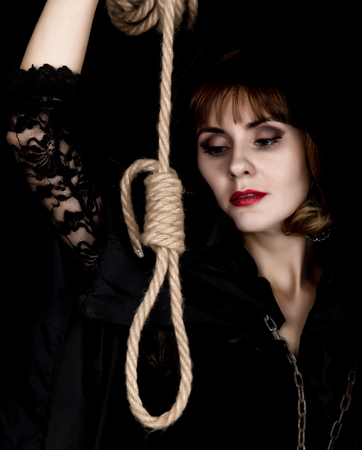 mysterious young woman holding loop of the rope. on a dark background. Stock Photo