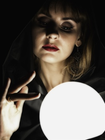 mysterious young woman wonders on a large luminous ball. on a dark background.