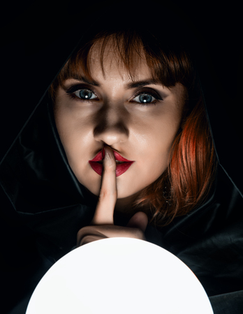 mysterious young woman wonders on a large luminous ball and raised a finger to her lips. on a dark background.