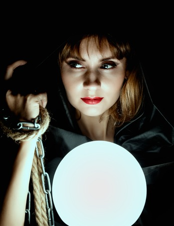 mysterious young woman holding loop of the rope and large glowing ball. on a dark background.