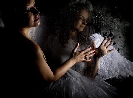 rudeness: Portrait of angel and devil womans on a dark background, behind transparent glass covered by water drops Stock Photo