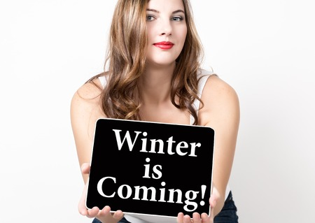 review site: winter is coming written on virtual screen. technology, internet and networking concept. beautiful woman with bare shoulders holding pc tablet.