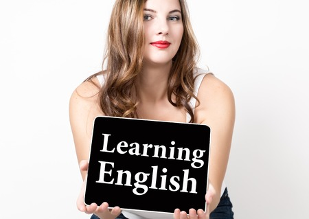 learning english written on virtual screen. technology, internet and networking concept. beautiful woman with bare shoulders holding pc tablet.
