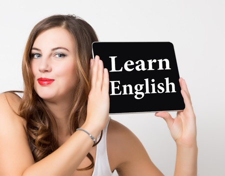 review site: learn english written on virtual screen. technology, internet and networking concept. beautiful woman with bare shoulders holding pc tablet.