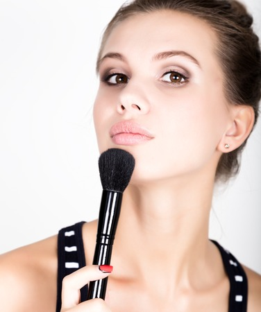 loose skin: Female model applying makeup on her face. Beautiful young woman applying foundation on her face with a make up brush