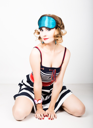 beautiful young woman in a striped dress and points for sleep, sitting on a floor and posing. sleeping eye covering mask.