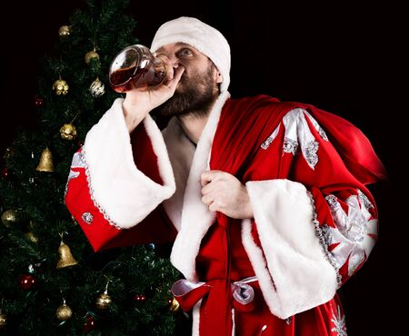 rudeness: rutal Santa Claus carries a bag, smiling spitefully and drinking brandy from a bottle, on the background of Christmas tree.