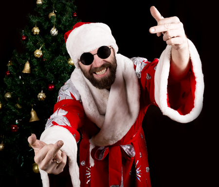 rudeness: bad brutal Santa Claus smiles and showing middle finger sign on the background of Christmas tree.