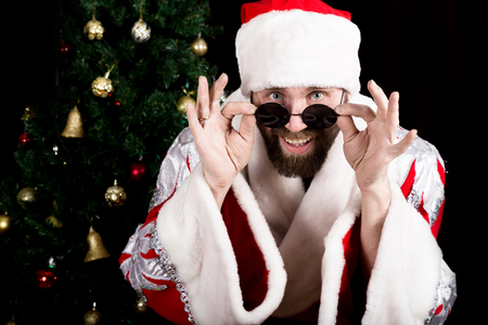 rudeness: bad rastoman Santa Claus holds round glasses and smiles, on the background of Christmas tree. different funy emotions.