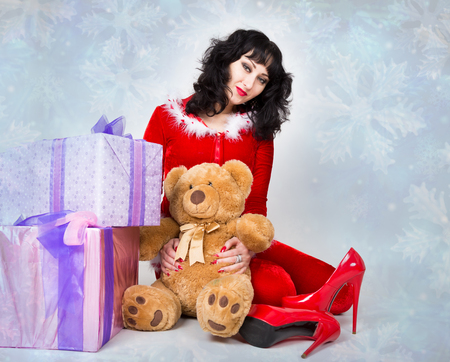 young and beautiful woman in red coat holding a nice Christmas present box.