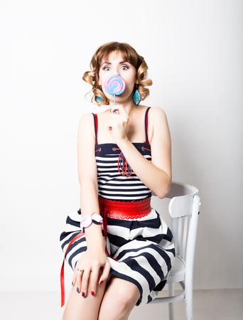 beautiful young woman in a striped dress eats a lollipop.