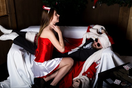 sexy nurse: drunk santa claus lying on sofa, female nurse sexy woman in carnival costume, tries to wake him up. Stock Photo