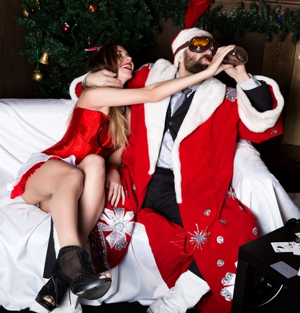 sexy nurse: drunk santa claus with female nurse sexy woman in carnival costume drinking brandy.