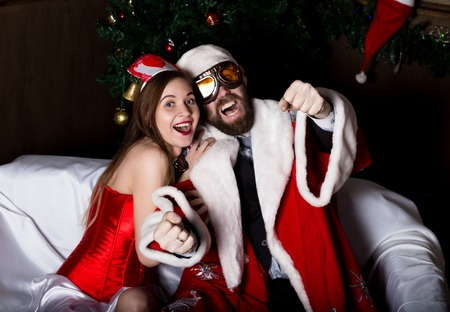sexy nurse: brutal Santa Claus with female nurse sexy woman in carnival costume, driving on couch like on a car.