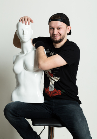 Expressive young rocker man posing with dummy.