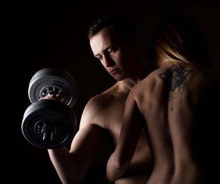 execute: beautiful young sporty sexy couple showing muscle on a dark background.