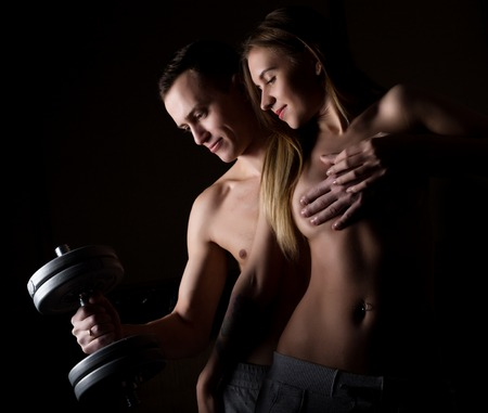 musculation: beautiful young sporty sexy couple showing muscle on a dark background.