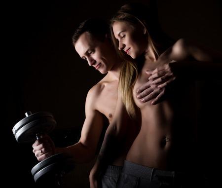 schöne junge sportliche sexy Paar zeigt Muskeln auf einem dunklen Hintergrund. Standard-Bild