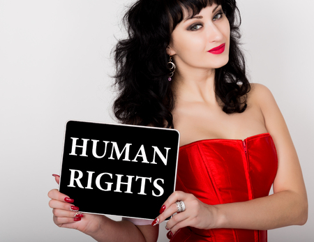 red corset: human rights written on virtual screen. technology, internet and networking concept. sexy woman in a red corset holding pc tablet.