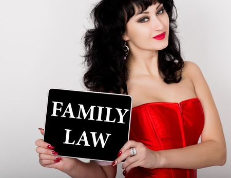 red corset: family law written on virtual screen. technology, internet and networking concept. sexy woman in a red corset holding pc tablet.