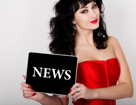 red corset: news written on virtual screen. technology, internet and networking concept. sexy woman in a red corset holding pc tablet. Stock Photo