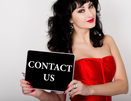red corset: contact us written on virtual screen. technology, internet and networking concept. sexy woman in a red corset holding pc tablet. Stock Photo