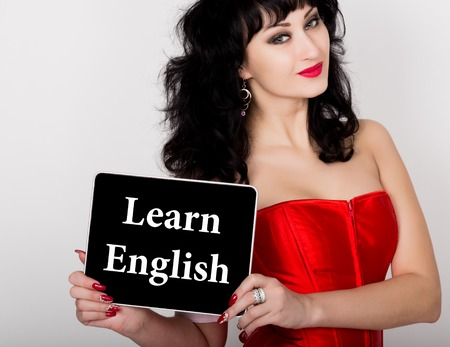 red corset: learn english written on virtual screen. technology, internet and networking concept. sexy woman in a red corset holding pc tablet.