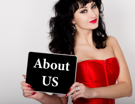 red corset: about us written on virtual screen. technology, internet and networking concept. sexy woman in a red corset holding pc tablet. Stock Photo
