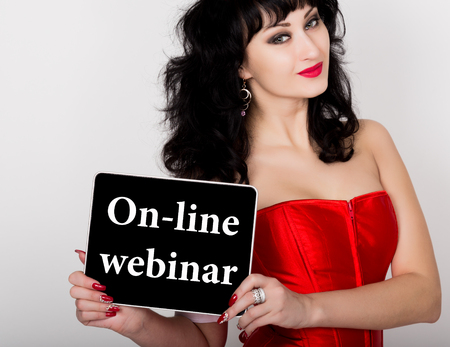 red corset: on-line webinar written on virtual screen. technology, internet and networking concept. sexy woman in a red corset holding pc tablet. Stock Photo