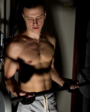 Handsome athletic man with dumbbell on a darck background. Standard-Bild