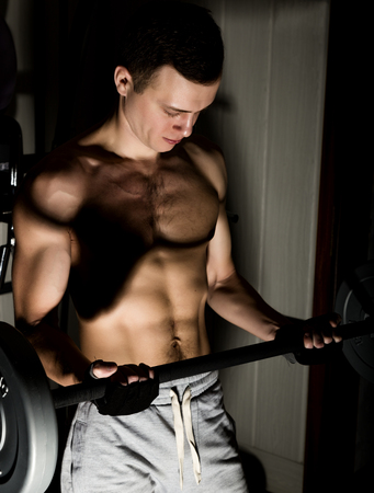 sixpack: Handsome athletic man with dumbbell on a darck background. Stock Photo