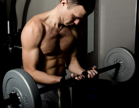 darck: Handsome athletic man with dumbbell on a darck background. Stock Photo