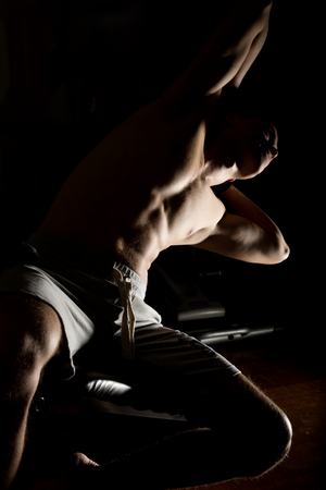 Handsome athletic man doing exercises in a gym on a darck background. Stock Photo