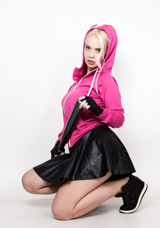 Playful young blonde in a tracksuit holding a baseball bat.