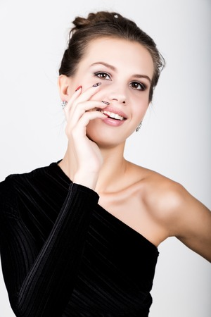 corrects: Portrait of the young woman in a black dress, holding hands near the face, she surprised. Stock Photo