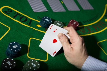 poker playing card on a green table background, man holding two aces.