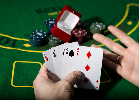 poker on a green table background, man holding losing combination of cards.