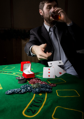 clubs diamonds: man in a business suit drinking brandy and throws cards with losing combination. casino chips, precious ring on green poker table. gambling addiction. Stock Photo