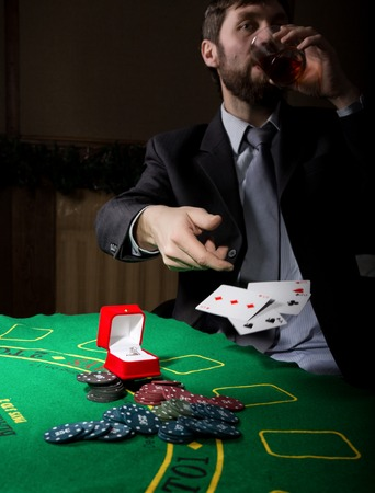 man in a business suit drinking brandy and throws cards with losing combination. casino chips, precious ring on green poker table. gambling addiction. Stock Photo