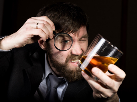 business skeptical: portrait of handsome young businessman looking at brandy through magnifying glass.