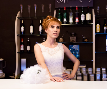bucket of money: Beautiful young redhead bride wearing white wedding dress with professional make-up and hairstyle standing at bar.